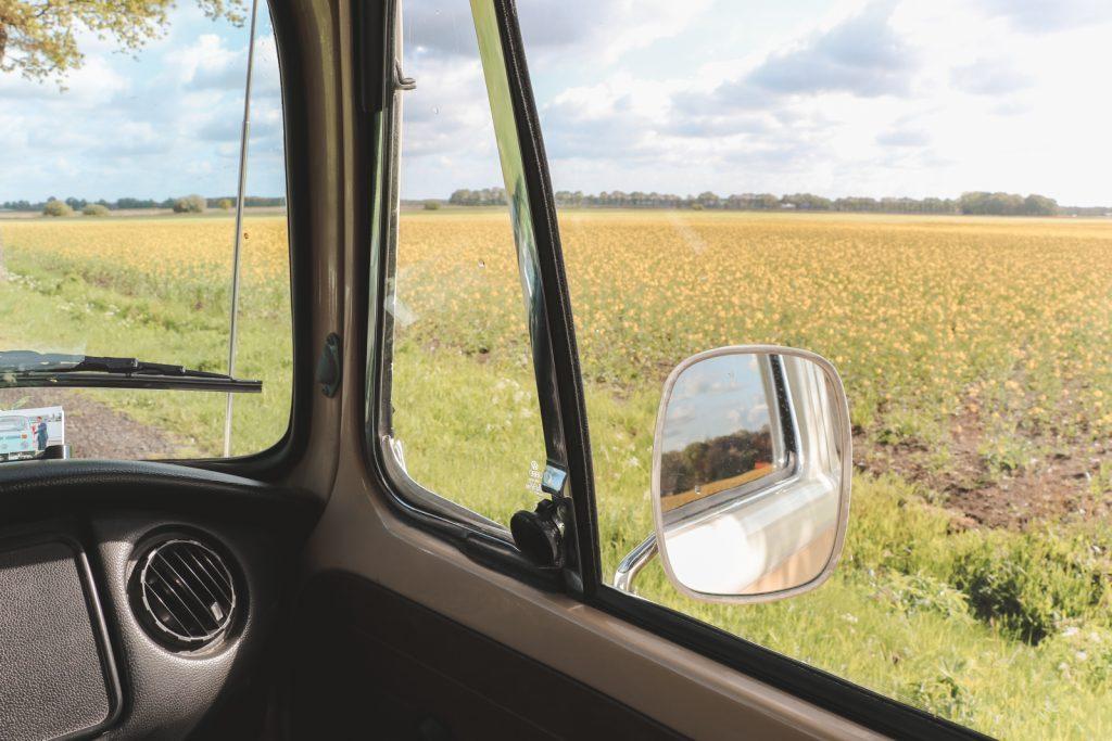 Uitzicht over gele bloemenvelden vanuit Volkswagen bus.