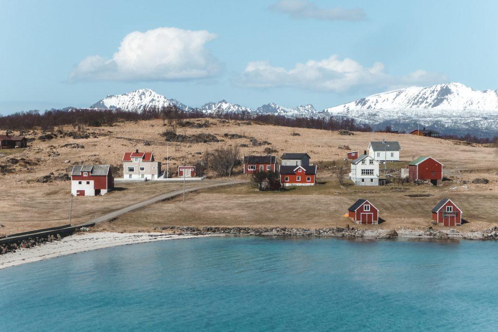 Traditionele houten Noorse huisjes aan rand van meer.