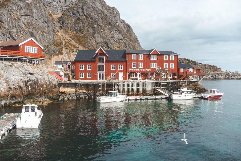 Klassieke rode houten Noorse huisjes aan blauw water.