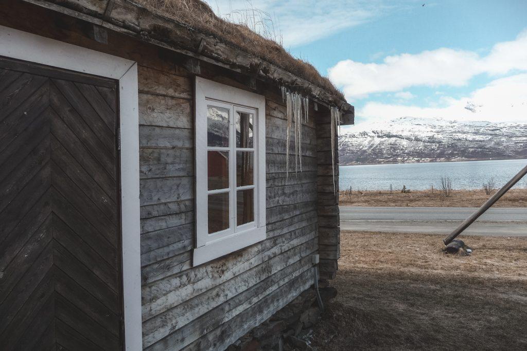 Houten huis met ijspegels en besneeuwde bergen op achtergrond.