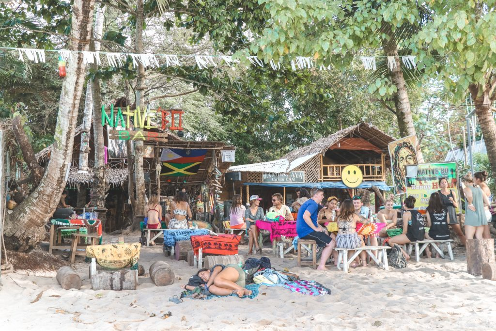 Toeristen bij bamboe café op strand Port Barton