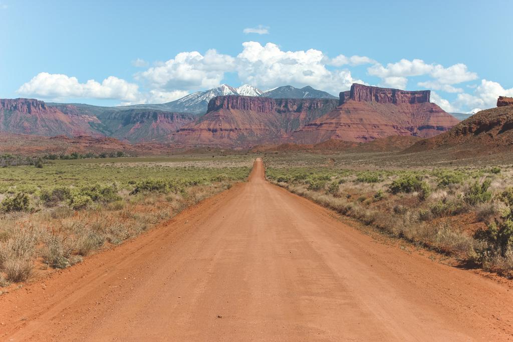 Stoffige zandweg richting rode bergen en sneeuw