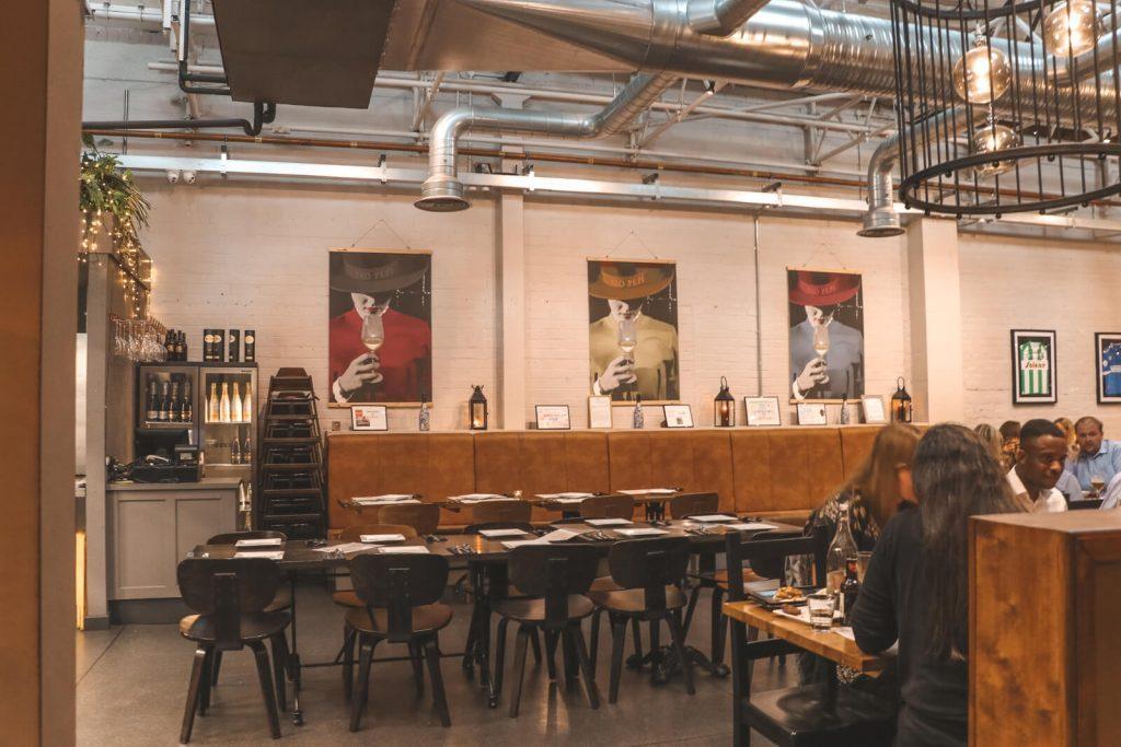 Houten tafels en industriële pijpen in tapasrestaurant Ambiente in Hull