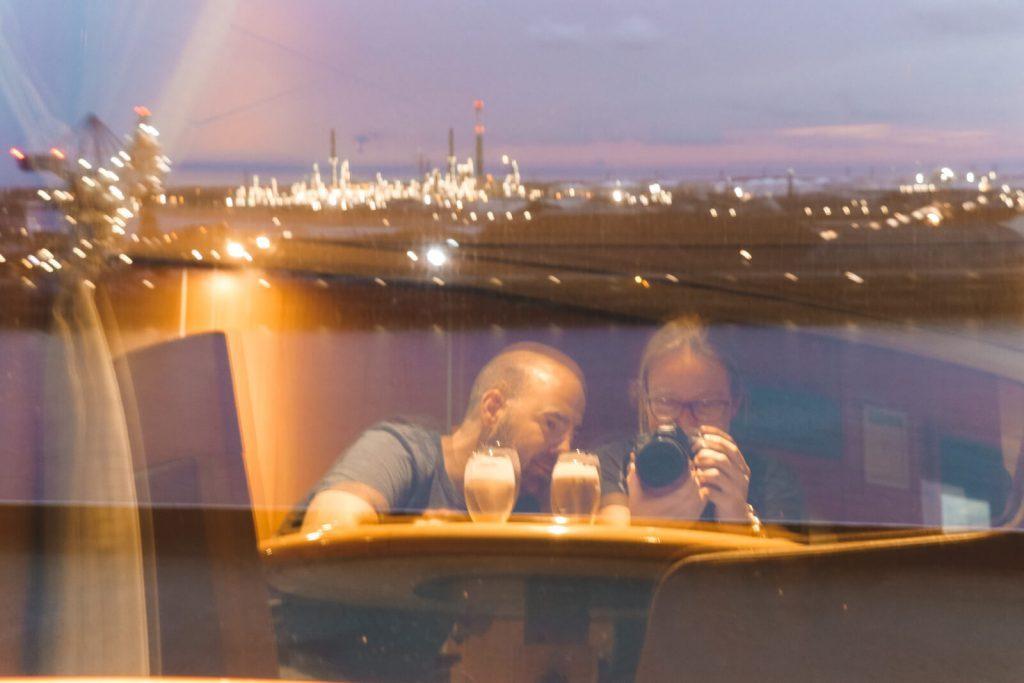 Spiegelbeeld van twee personen met op achtergrond Rotterdamse haven.