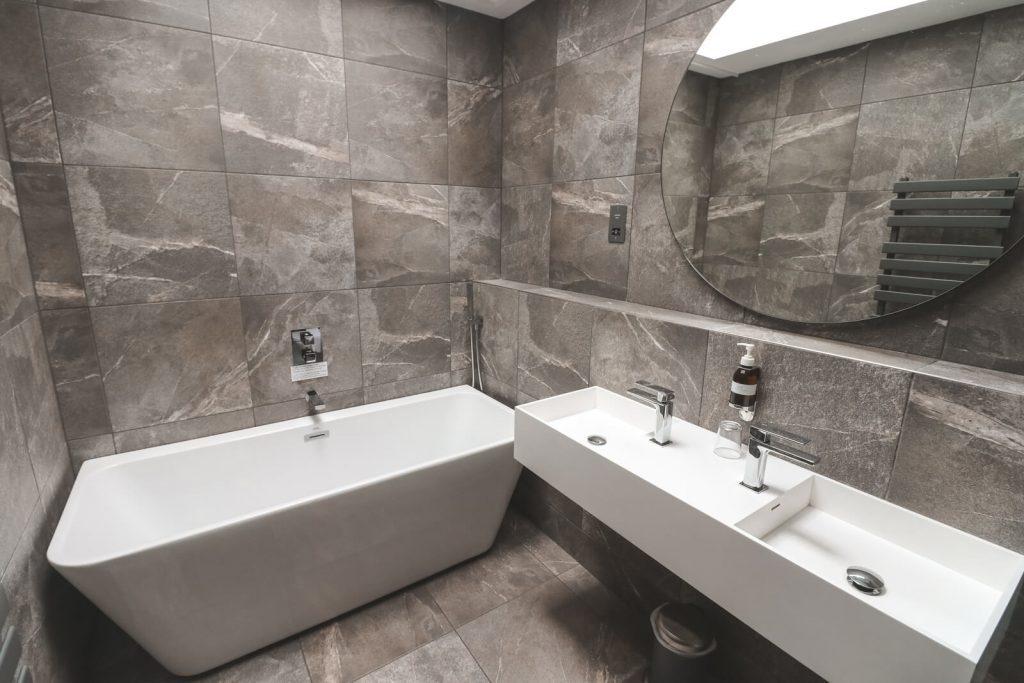 Grijze badkamer met wit ligbad Hideout Hotel Hull