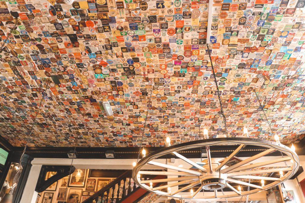 Honderden gekleurde bierviltjes aan plafond bij The Lion and Key
