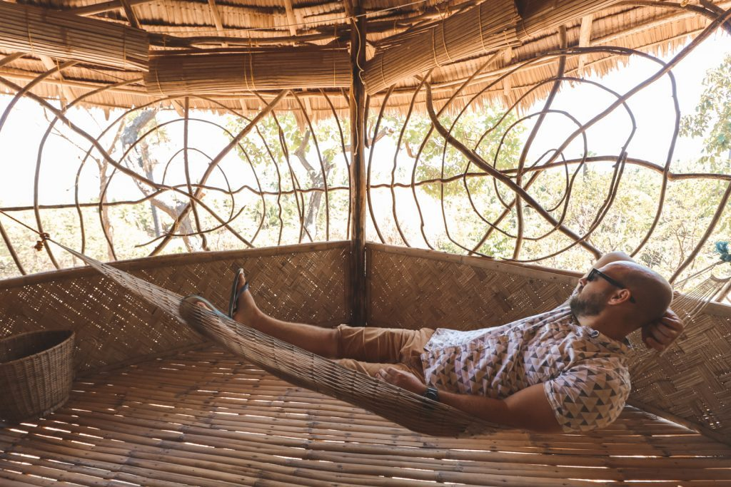 Man in hangmat in bungalow Sibaltan