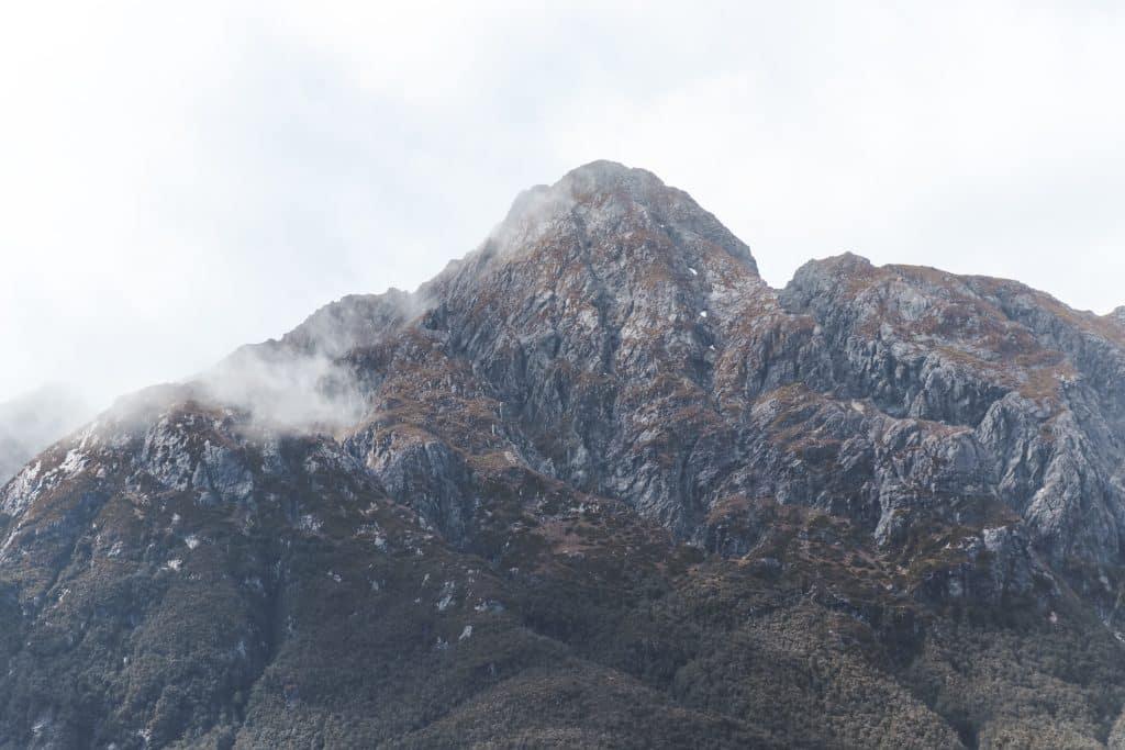 Wolken rondom grijze bergtoppen in Fiordland National Park Nieuw-Zeeland