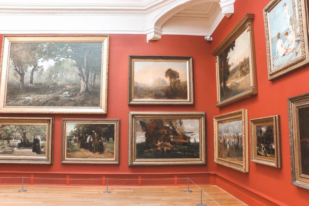 Middeleeuwse schilderijen tegen rode muur in Leeds Art Gallery