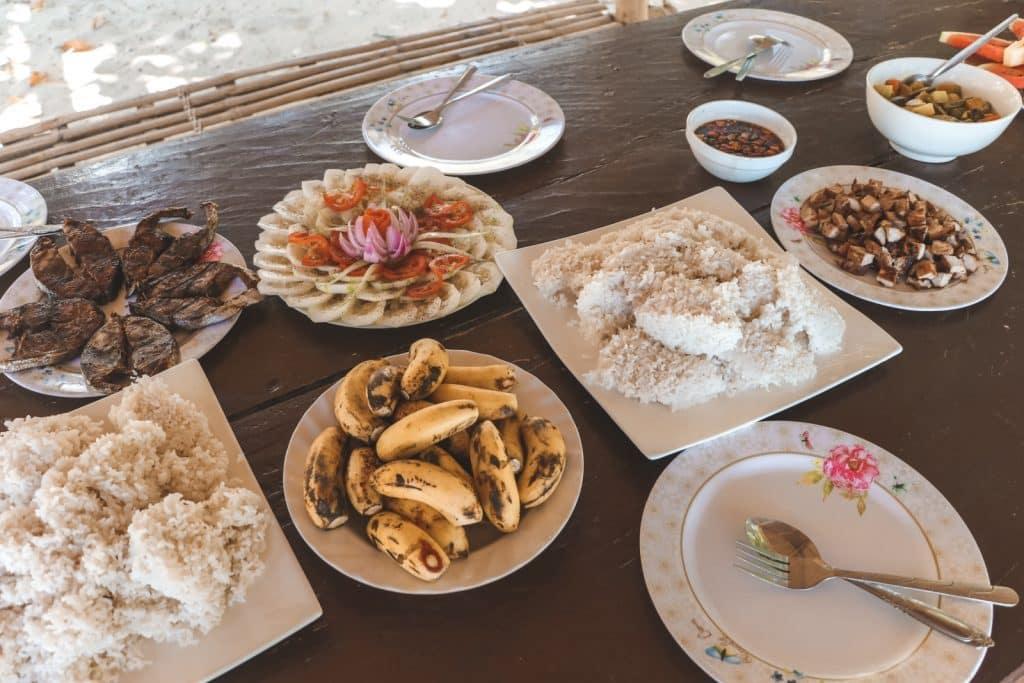 Borden met rijst, bananen, salades voor het snorkelen bij Sibaltan