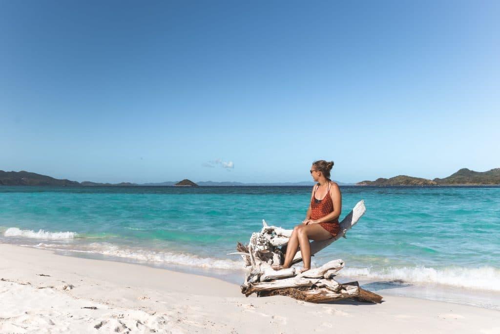 Vrouw op aangespoelde boomtak bij oceaan