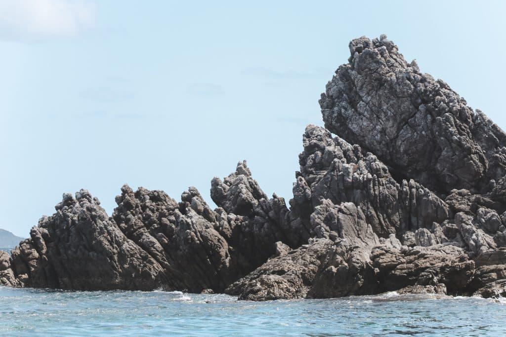 Grijze puntige rotsen in zee