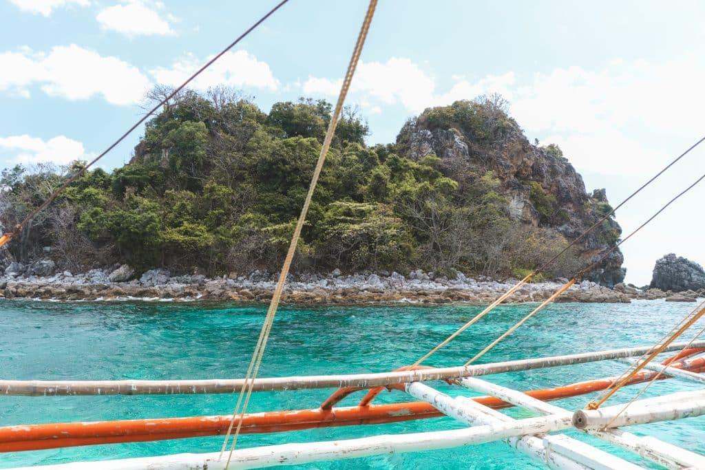 Rotsig Shark Island bij Palawan vanaf boot gezien