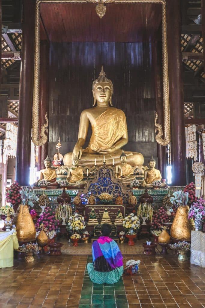 Vrouw bij gouden beeld van Boeddha