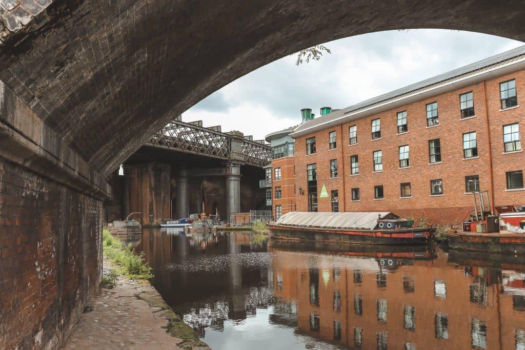 Stenen brug met smalle houten bootjes in kanaal