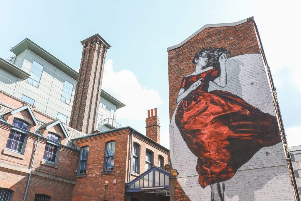 Street art van vrouw op hoge muur in Manchester genaamd Serenity van SNIK