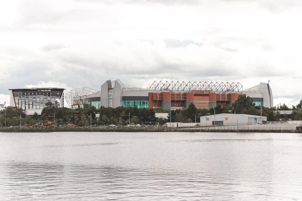 Water met op achtergrond voetbalstadion van Manchester United