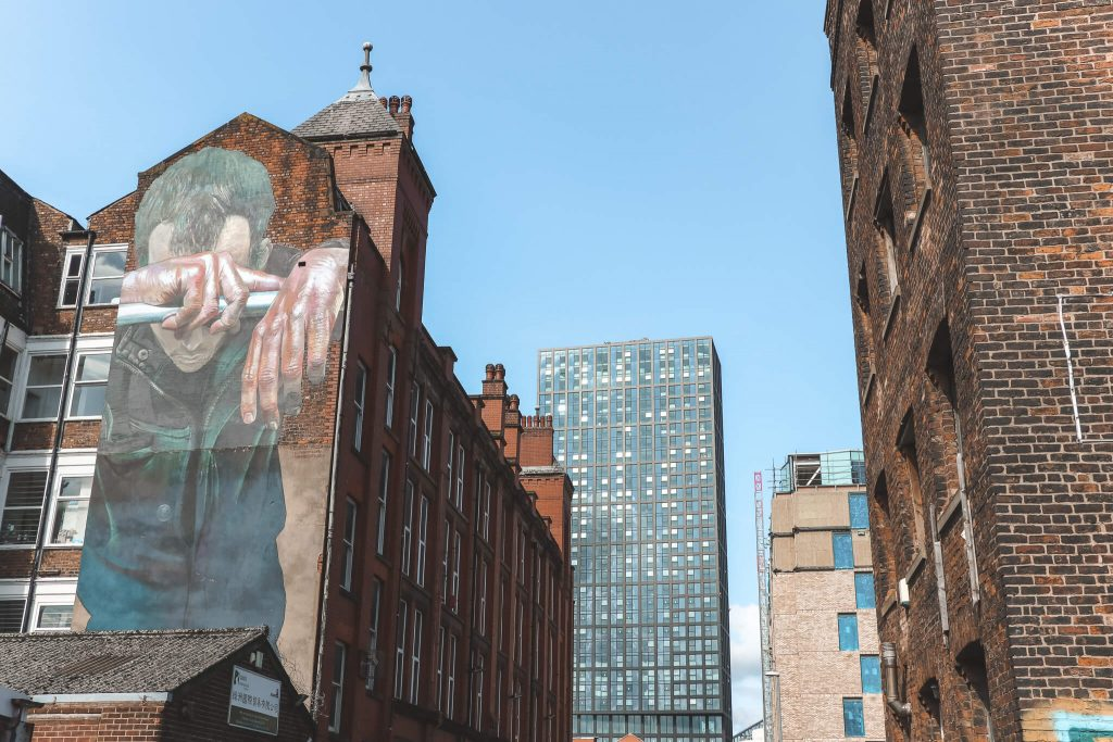 Kunstwerk van emotionele man op muur in Manchester
