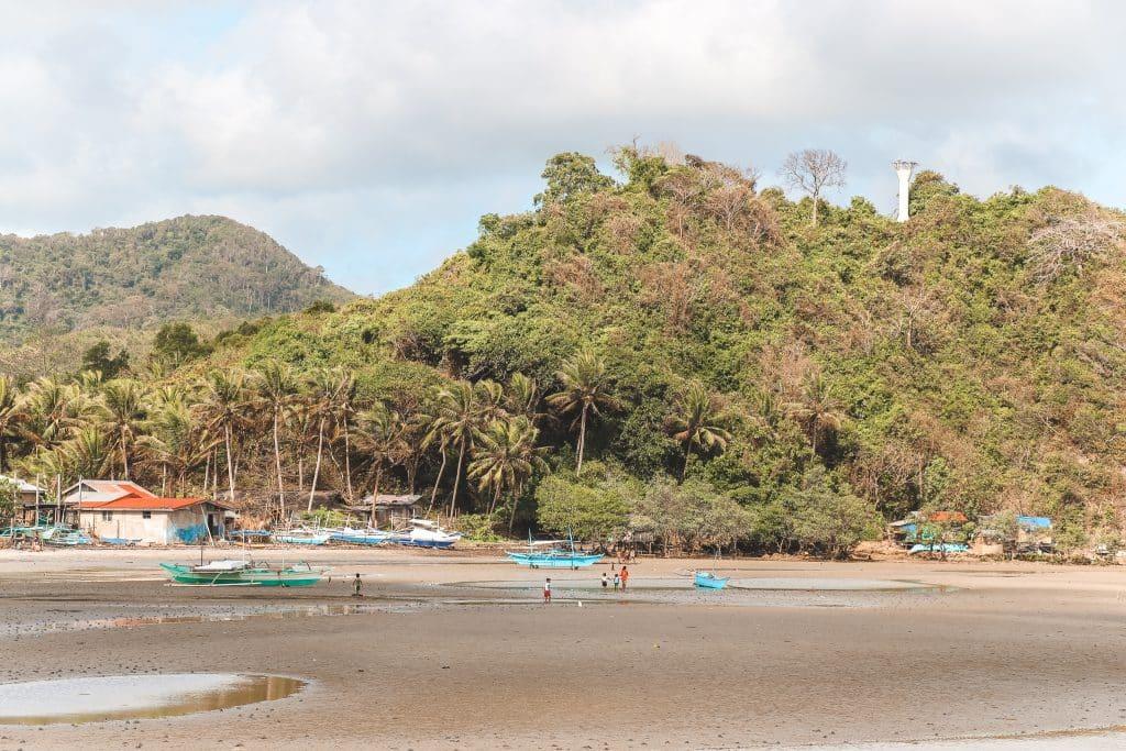 Boten op het zand met groene bergen op achtergrond