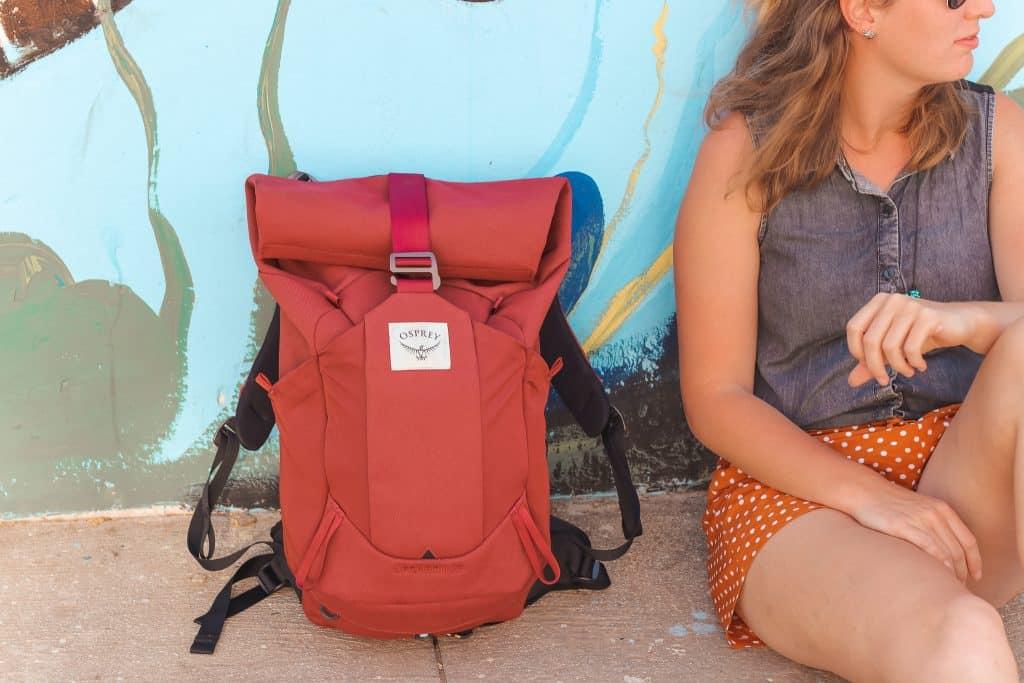 Rode Osprey backpack tegen muur met graffiti