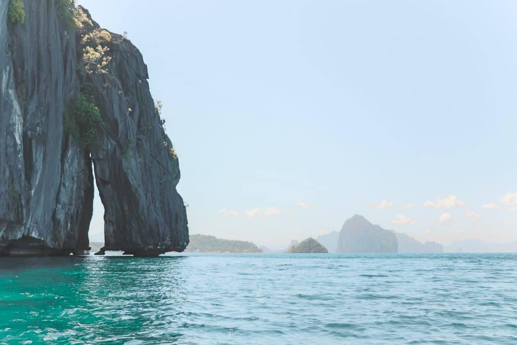 Scheve rots tegen rotswand in oceaan bij El Nido