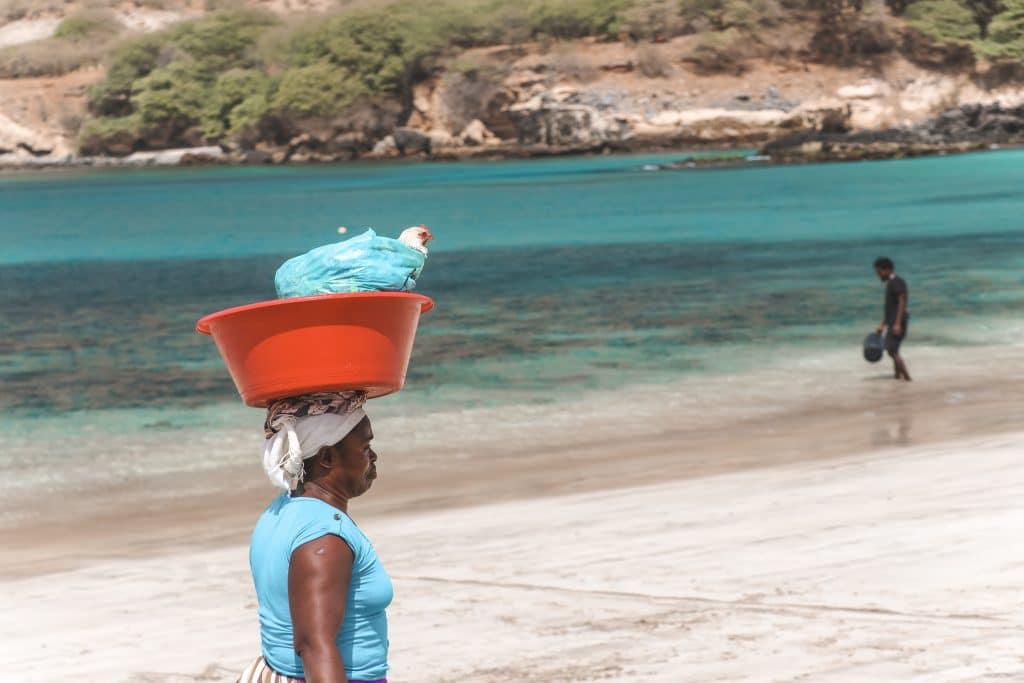 Vrouw met kip op strand Kaapverdië