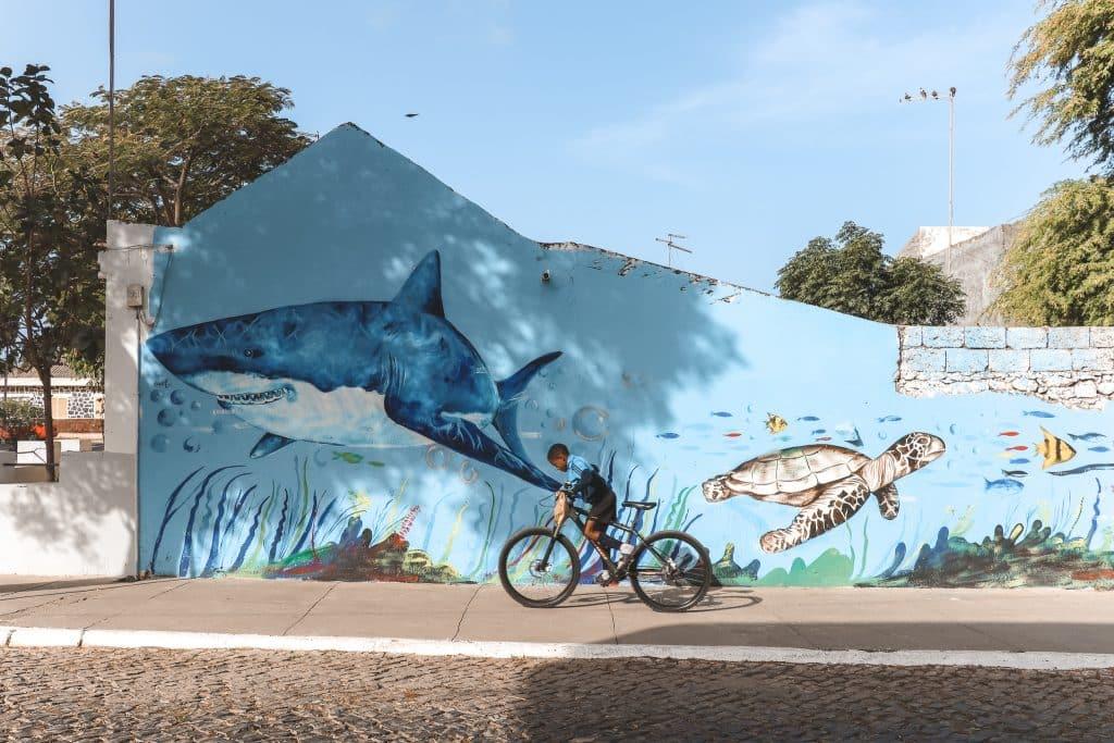 Blauwe muur met street art van haai en schildpad in Tarrafal, Kaapverdië