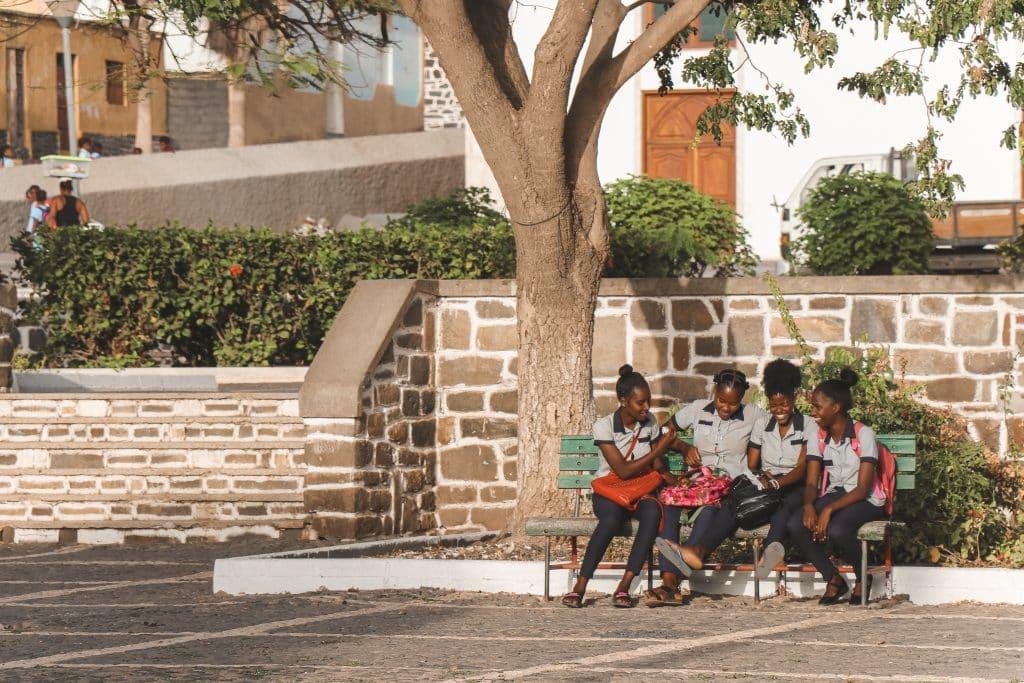 Scholieren op bankje voor stenen muur Kaapverdië