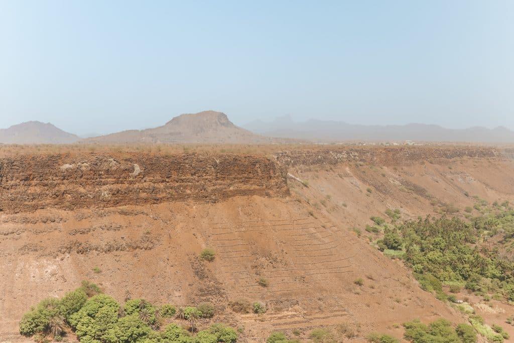 Uitzicht over uitgedroogd landschap met een paar groene struikjes bij Cidade Velha