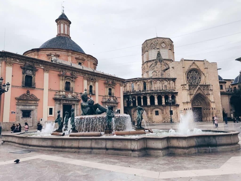 Fontein voor roze historisch gebouw op Plaza de La Virgen in Valencia
