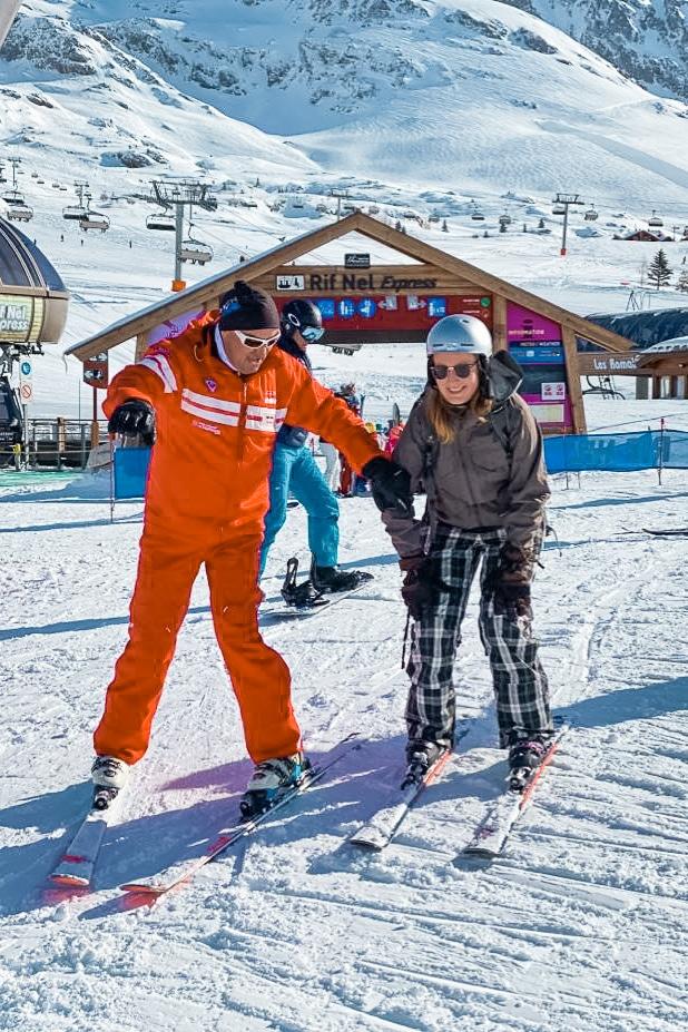 Leren skiën als volwassene met skileraar in rood pak