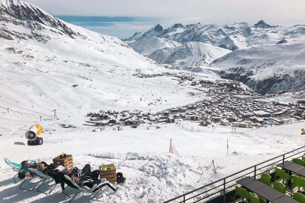 Mensen op strandstoelen in bergen met sneeuw