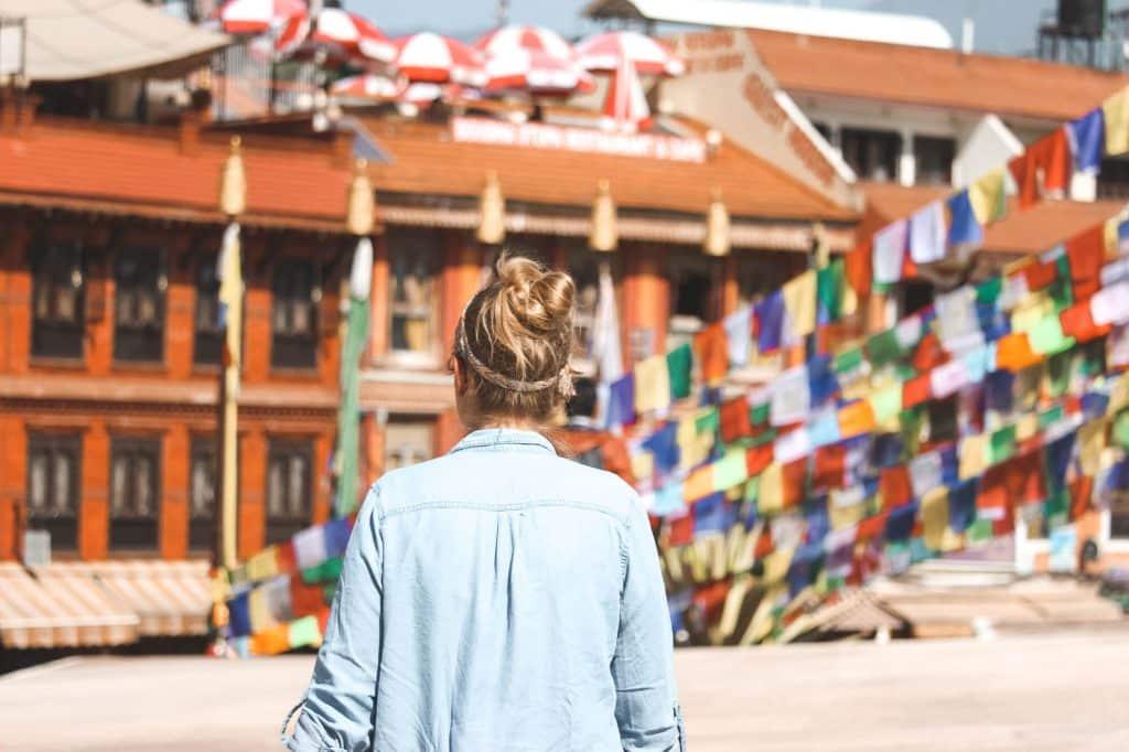 Vrouw die richting rood gebouw in Kathmandu, Nepal loopt